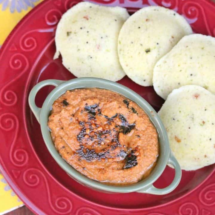 orange color chutney with seasonings on top and idli on side