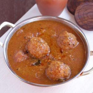 Kuzhambu made with lentil balls in a steel bowl