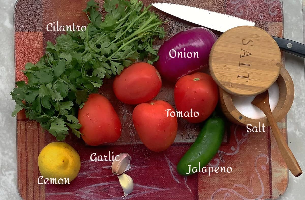 tomatoes, garlic, onion, cilantro, jalapeno, lemon and salt on a cutting board